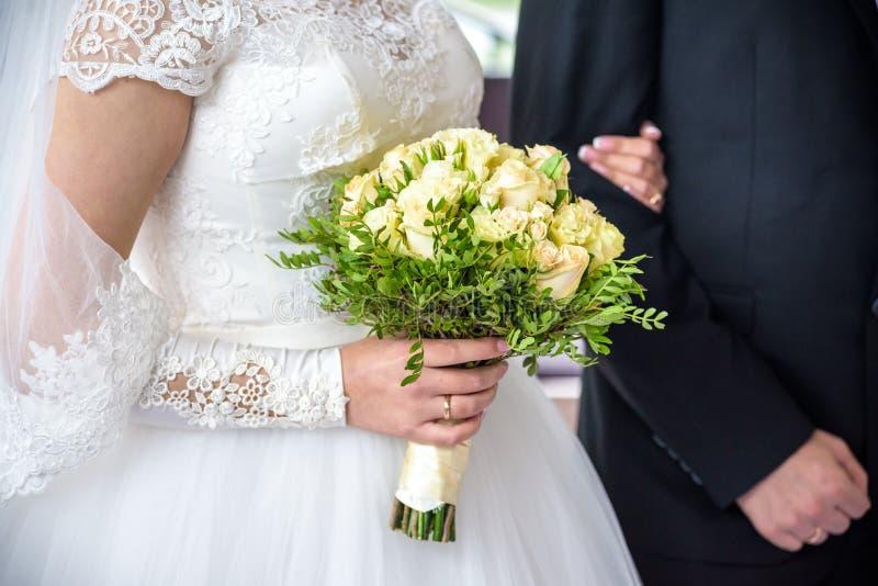 Жених и невеста держит руки ` s одина другого во время свадебной церемонии церков стоковое фото rf