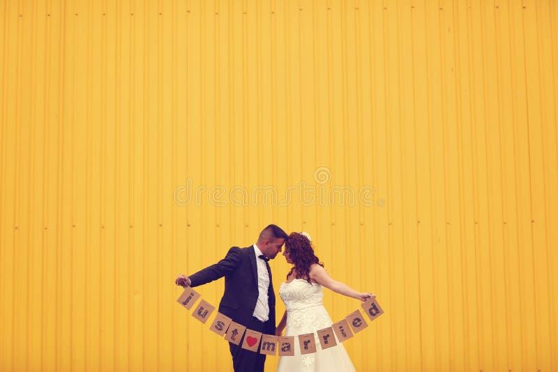 Жених и невеста держа как раз пожененный знак стоковая фотография