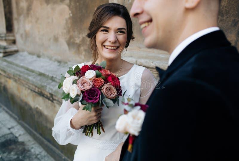Жених и невеста идя в солнечный город на больших зданиях стоковое изображение