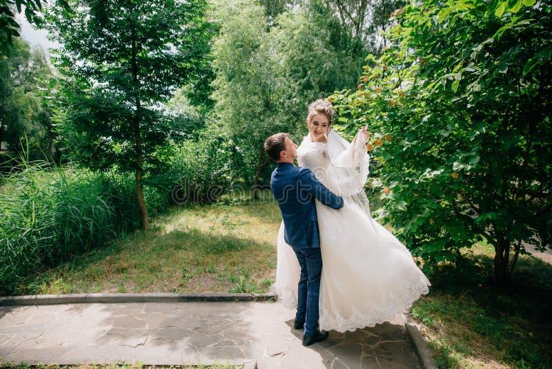 Жених и невеста имеет потеху в парке, человек поднял его любимое в его оружиях и поворачивает ее вокруг в ее стоковые фото