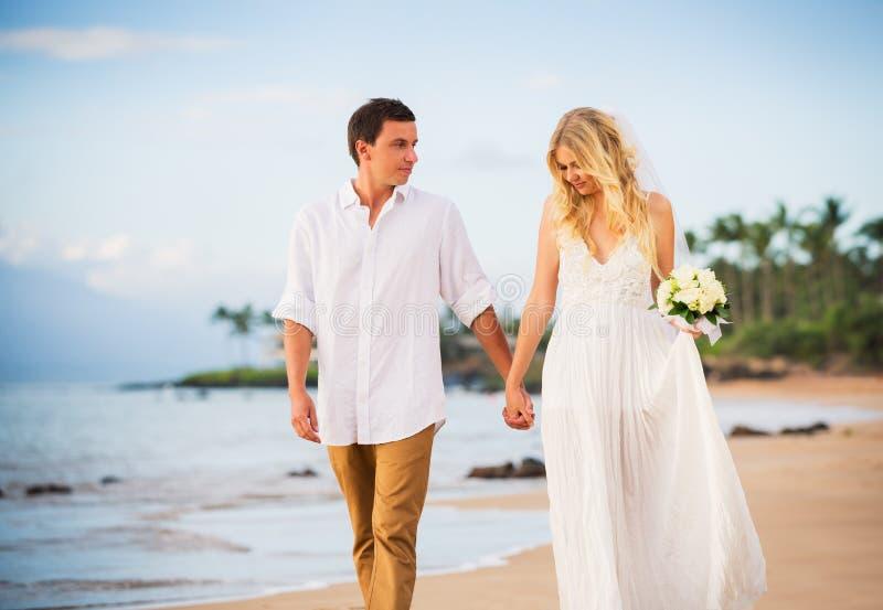 Жених и невеста, идя на красивый тропический пляж на заходе солнца стоковая фотография rf