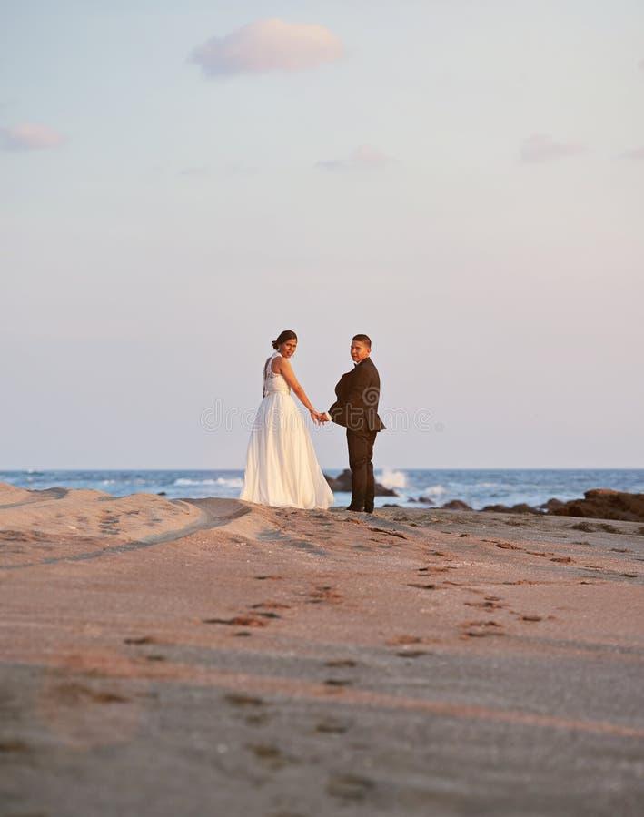 Жених и невеста идя на тропический пляж стоковые фотографии rf