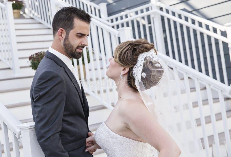 Жених и невеста лицом к лицу на лестницах стоковое изображение rf