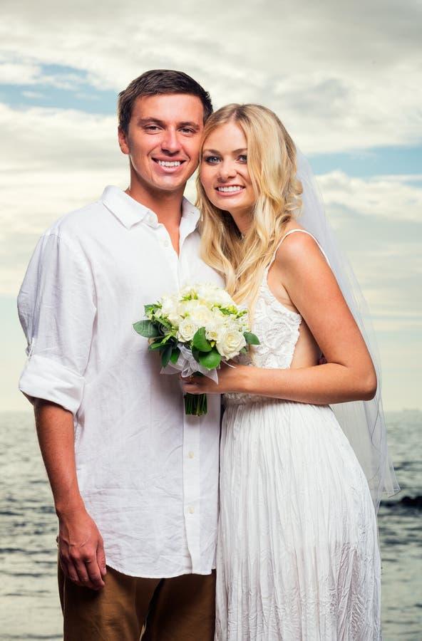 Жених и невеста на заходе солнца на тропическом пляже стоковое изображение rf