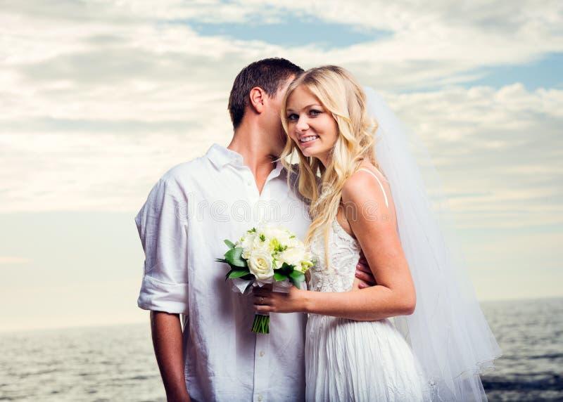 Жених и невеста на заходе солнца на тропическом пляже стоковое изображение