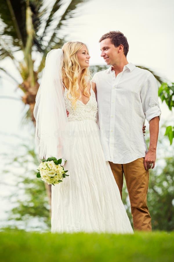 Жених и невеста на заходе солнца на тропическом пляже стоковая фотография rf