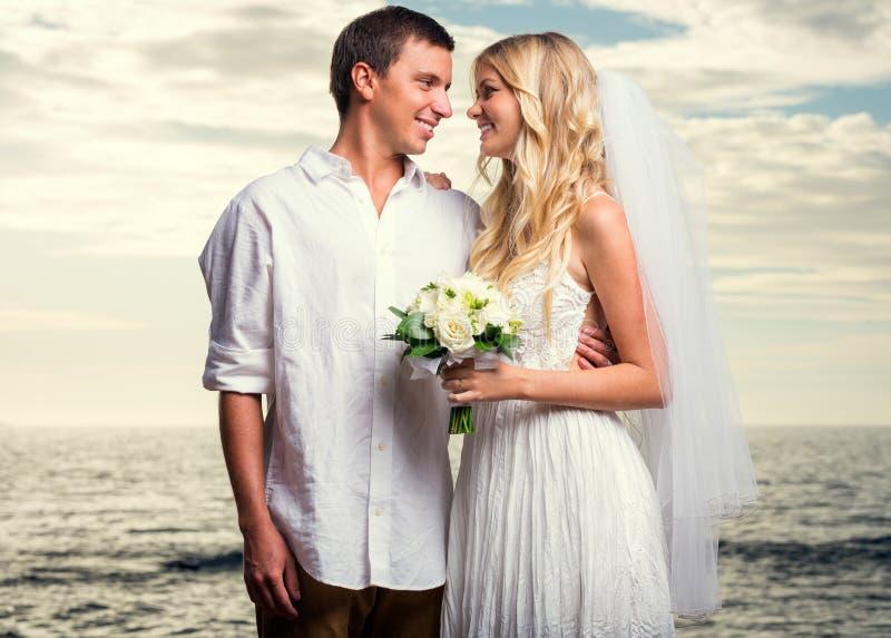 Жених и невеста на заходе солнца на тропическом пляже стоковые фото