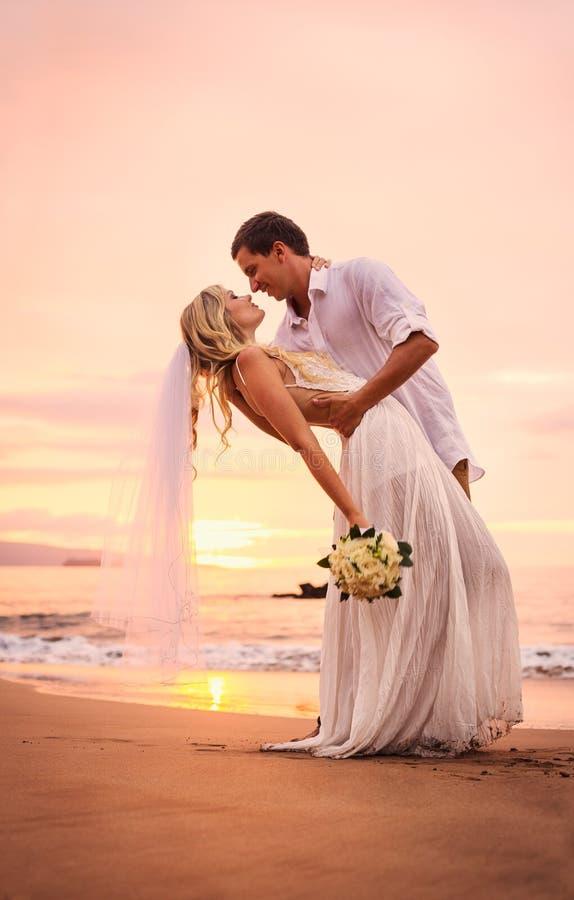 Жених и невеста на пляже на заходе солнца стоковая фотография rf