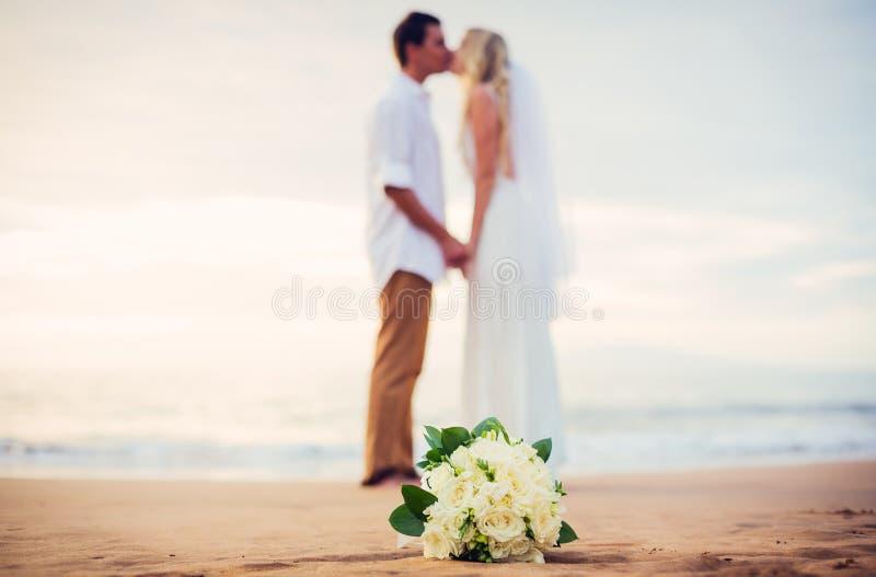Жених и невеста на пляже на заходе солнца стоковое фото rf