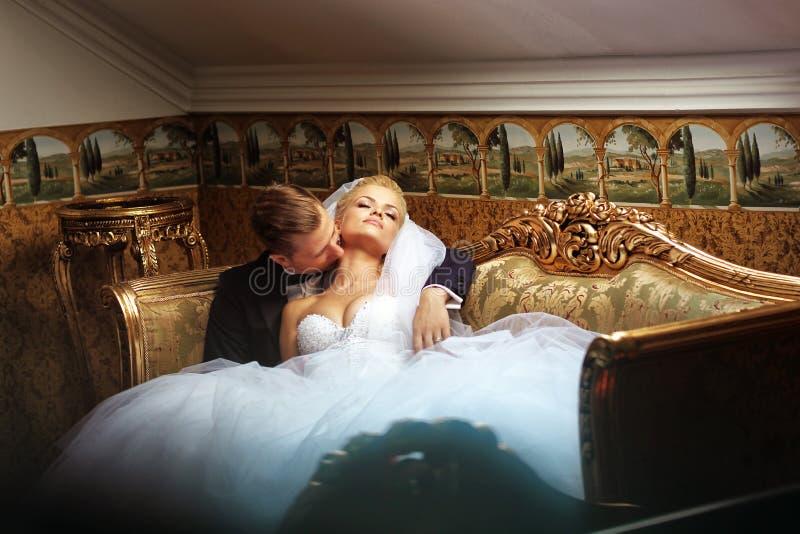 Жених и невеста на роскошной гостинице, целуя на софе стоковые фотографии rf