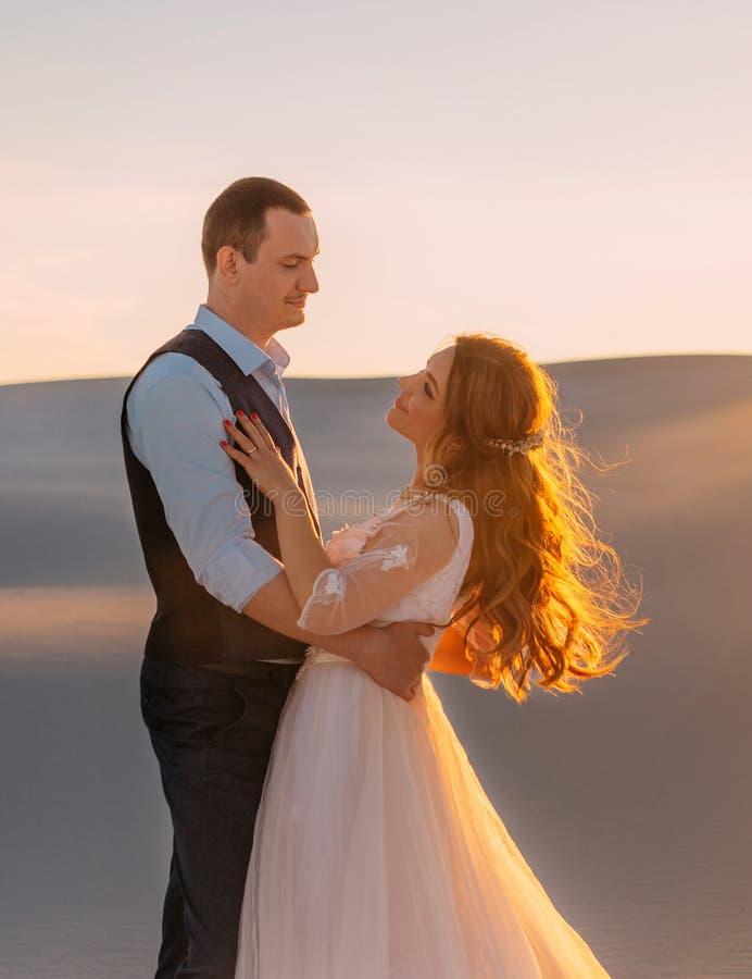 Жених и невеста обнимает в теплой солнечности на заходе солнца Красивая девушка брюнета с длинными взглядами волос на высокоросло стоковое изображение rf