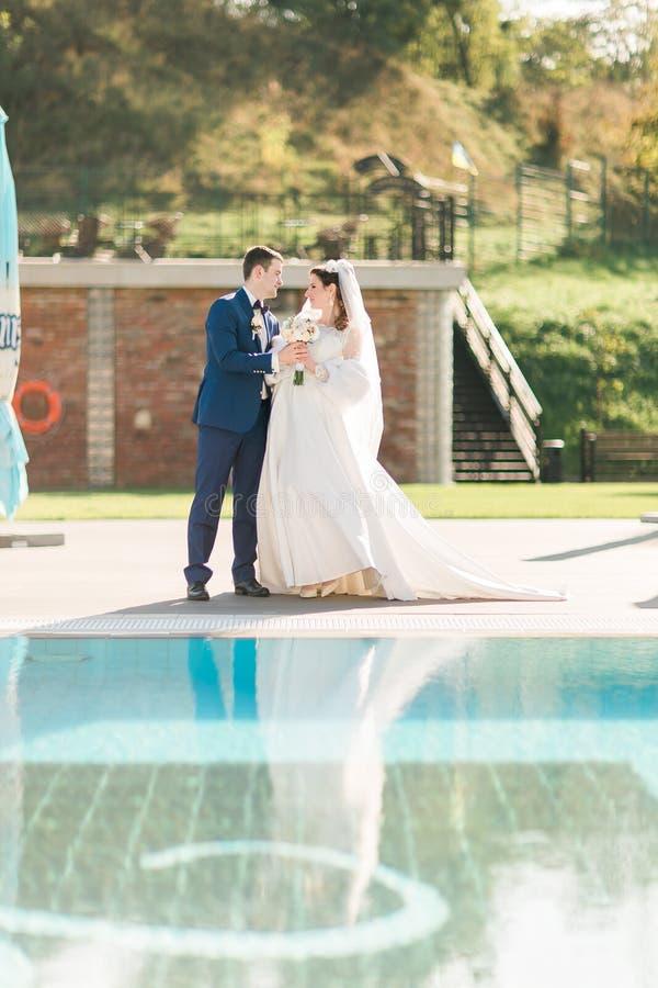 Жених и невеста около бассейна Укомплектуйте личным составом держать руку женщины в красивом платье стоковое фото rf