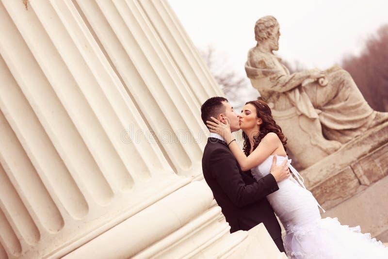 Жених и невеста около белых столбцов стоковые фотографии rf