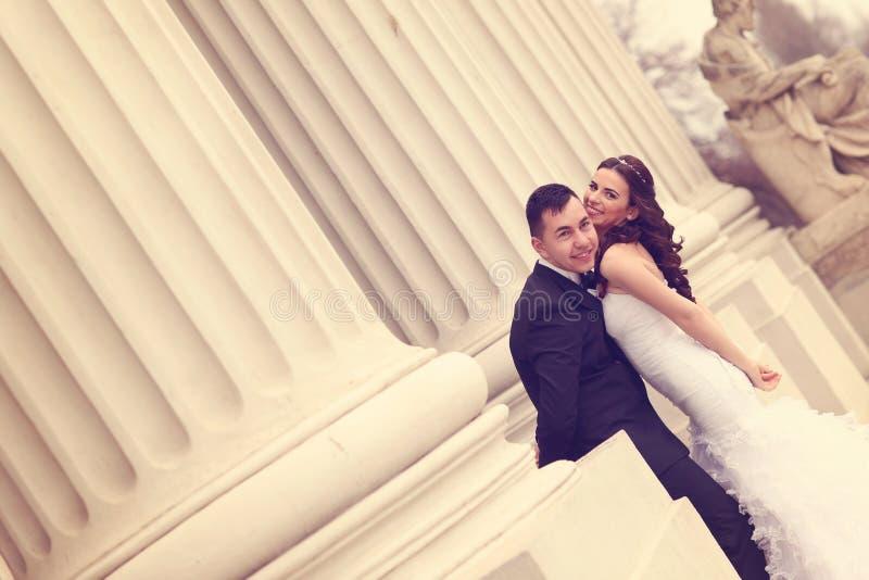 Жених и невеста около белых столбцов стоковая фотография