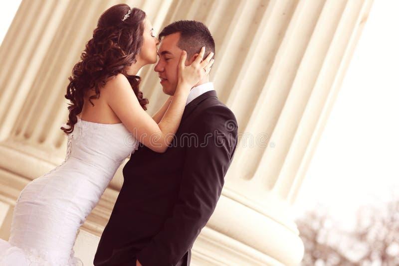 Жених и невеста около белых столбцов стоковое изображение rf