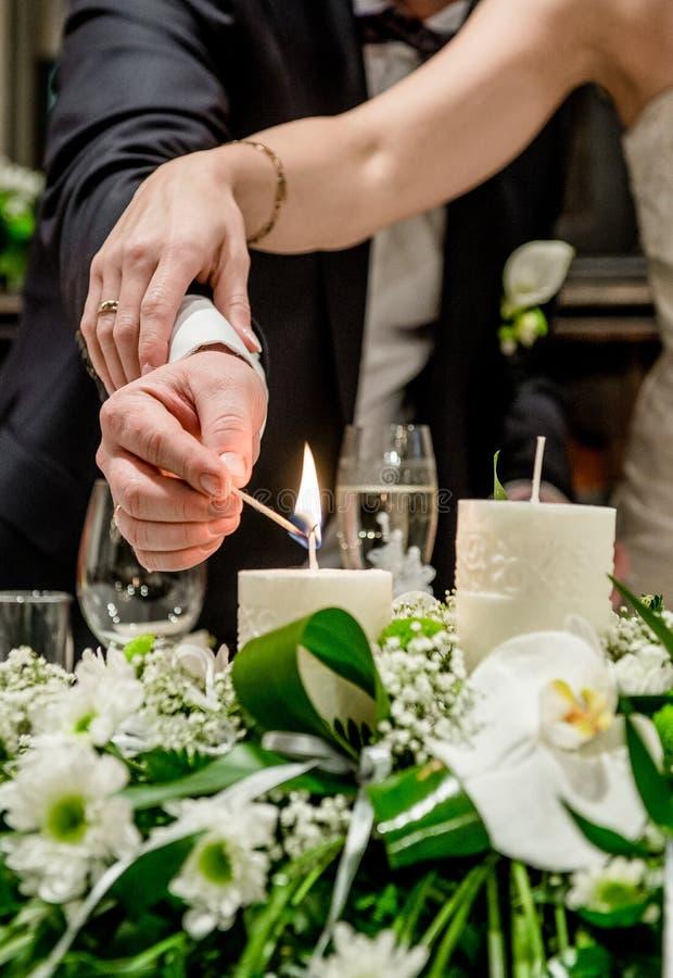 Жених и невеста освещая свечу стоковое изображение rf