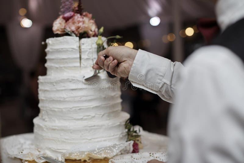 Жених и невеста отрезал деревенский свадебный пирог на банкете свадьбы с красной розой и другими цветками стоковая фотография