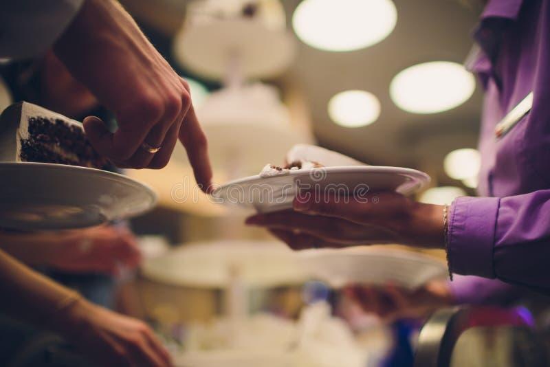 Жених и невеста отрезал деревенский свадебный пирог на банкете свадьбы с красной розой и другими цветками стоковые изображения
