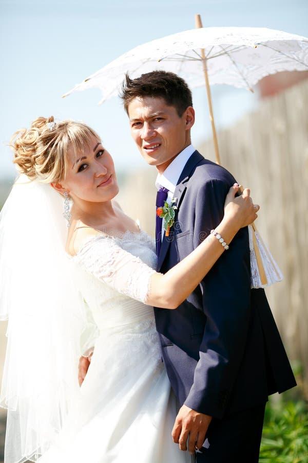 Жених и невеста под белым зонтиком на солнечный день стоковые фотографии rf
