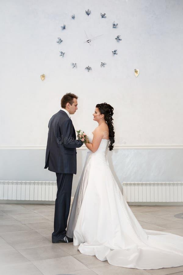 Жених и невеста под часами стоковое фото