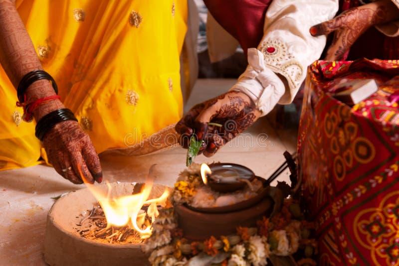 Жених и невеста предлагая к святому огню, типичный ритуал свадьбы во время замужества стоковое изображение rf