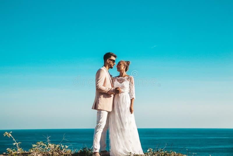 Жених и невеста представляя на скале за голубым небом и морем ювелирные изделия cravat пар кристаллические связывают венчание стоковые фотографии rf