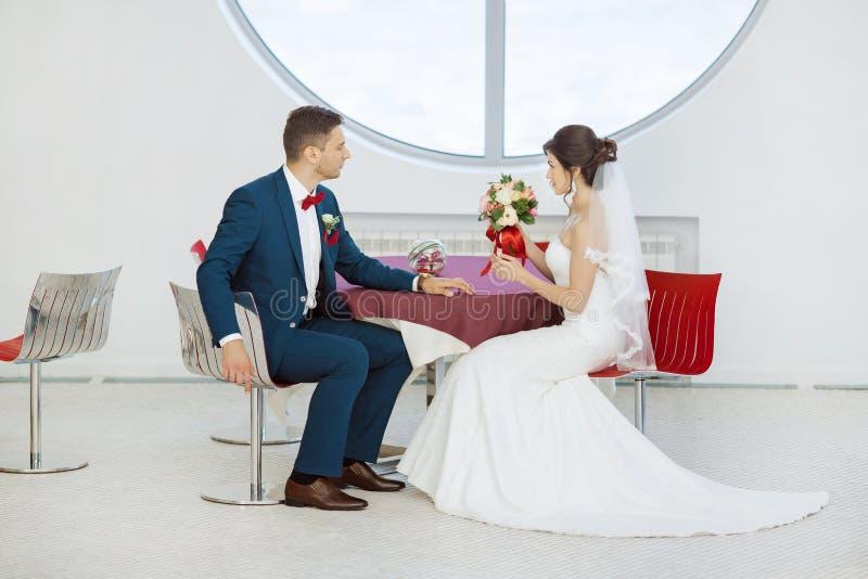 Жених и невеста сидя в внутри помещения кафе стоковые фото
