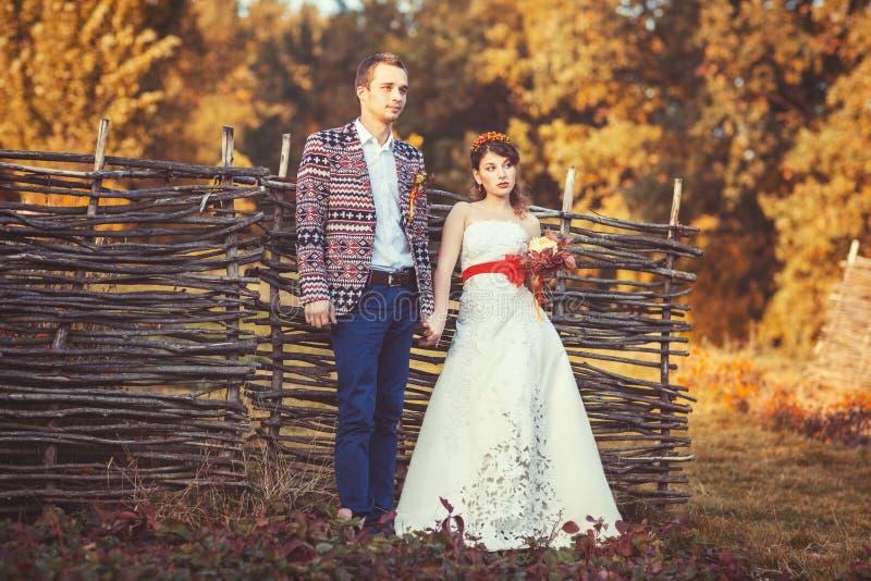 Жених и невеста стоя около плетеной загородки держа руки стоковые изображения rf
