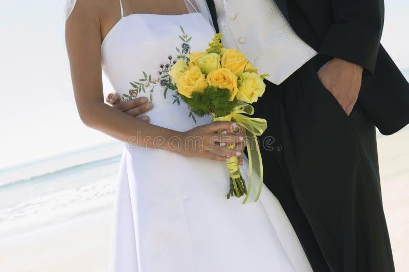 Жених и невеста с букетом на пляже (конец-вверх) стоковые изображения