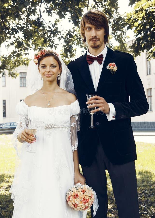 Жених и невеста с стеклами шампанского стоковые изображения