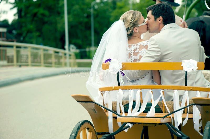 Жених и невеста целуя в экипаже стоковое изображение