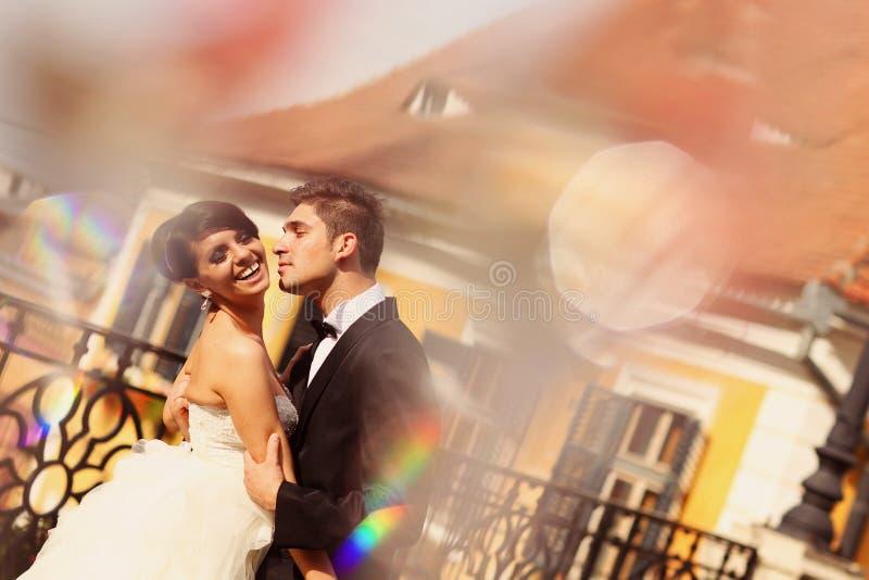 Жених и невеста целуя и обнимая в городе стоковые фотографии rf