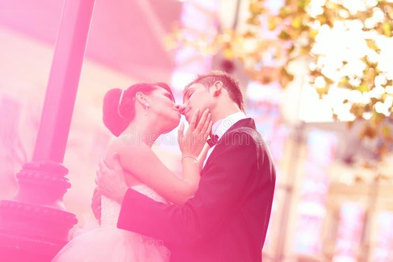 Жених и невеста целуя и обнимая в городе стоковое изображение
