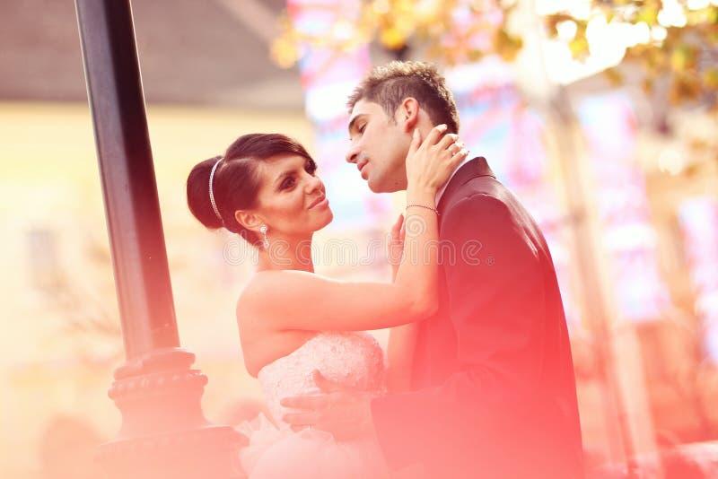 Жених и невеста целуя и обнимая в городе стоковые фото
