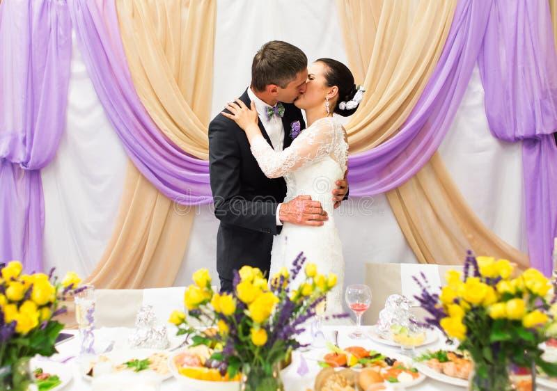 Жених и невеста целуя на приеме по случаю бракосочетания стоковые фото