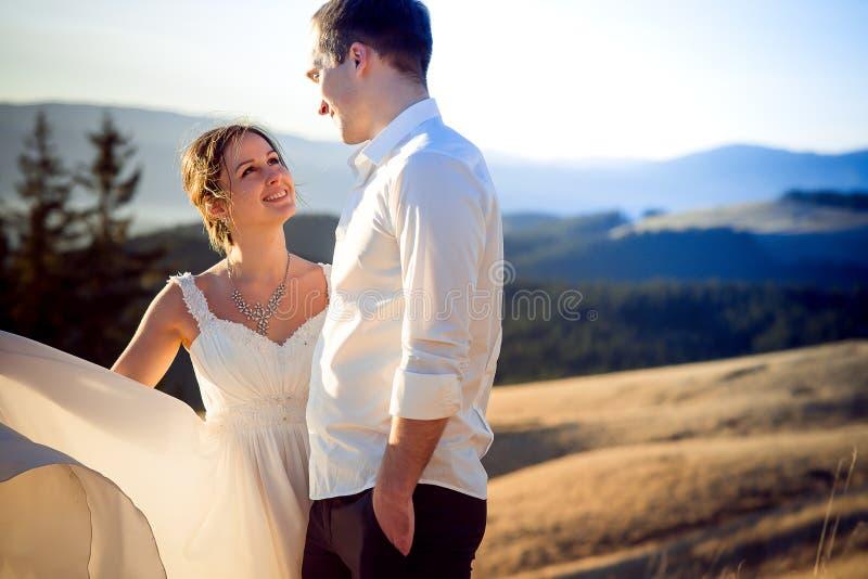 Жених и невеста любяще смотрит один другого Предпосылка гор стоковые фото