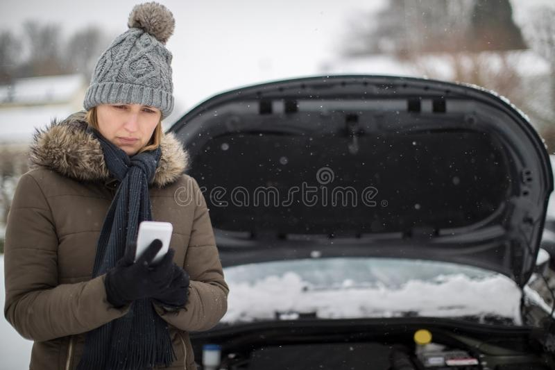 Женская автомобилистка сломанная вниз в снеге вызывая для обочины Assista стоковая фотография