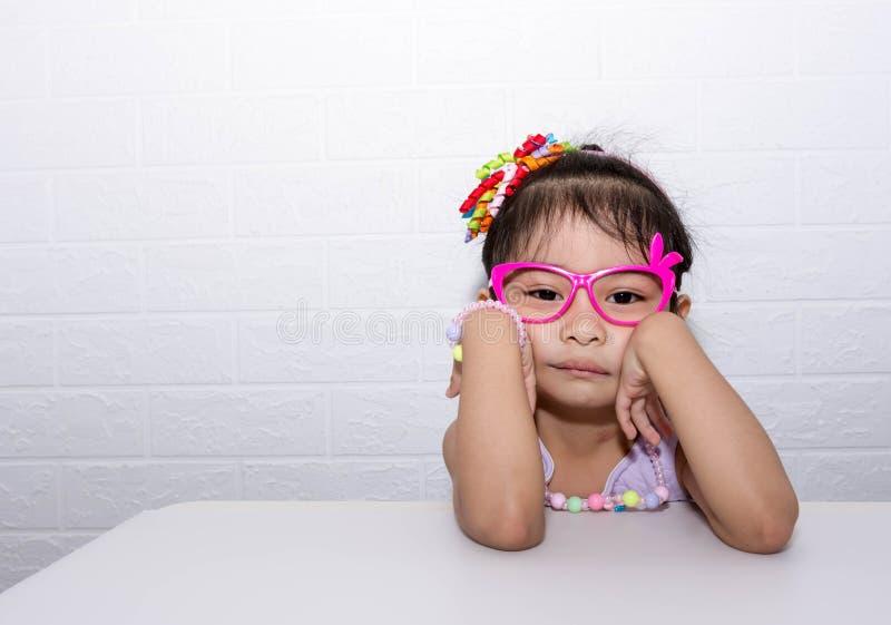 Женская азиатская девушка ребенка представляя дурацкое грустное сиротливое представление пока носящ некоторые аксессуары как крон стоковое изображение