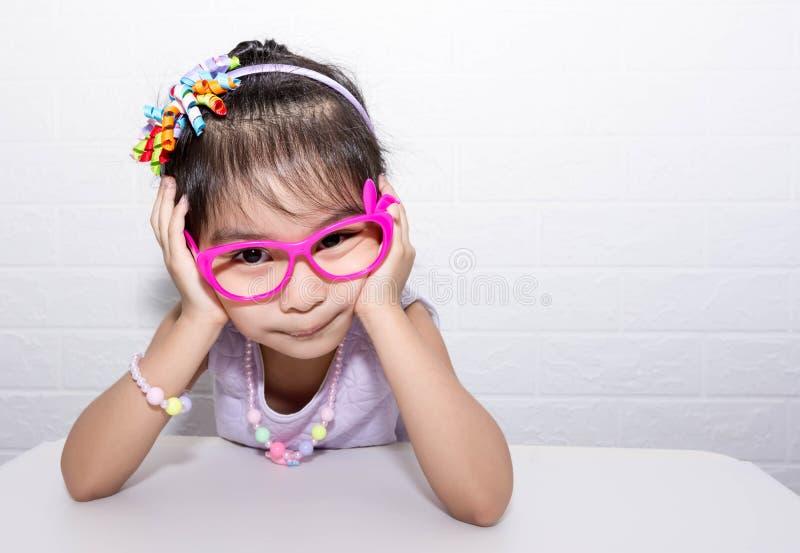 Женская азиатская девушка ребенка представляя дурацкое грустное сиротливое представление пока носящ некоторые аксессуары как крон стоковые изображения