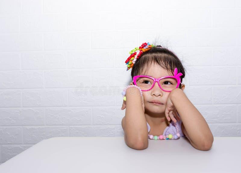 Женская азиатская девушка ребенка представляя дурацкое грустное сиротливое представление пока носящ некоторые аксессуары как крон стоковое фото rf