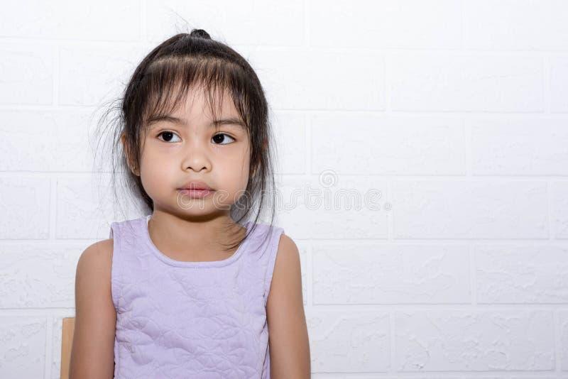Женская азиатская девушка ребенка сидя на стуле с белой предпосылкой стоковое фото