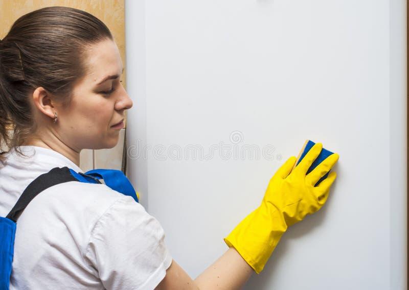 Женская дверь холодильника чистки привратника стоковая фотография