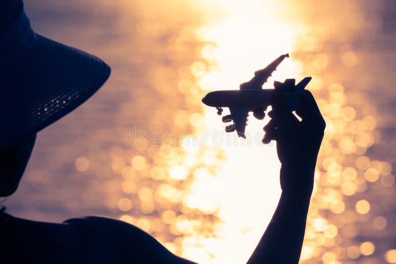 Женская держа игрушка самолета на заходе солнца стоковая фотография