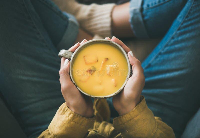 Женская держа кружка супа сливк тыквы желтого в руках стоковое фото