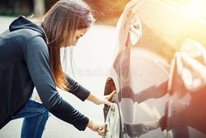 Женская изменяя автошина с ключем колеса с светом солнца стоковая фотография