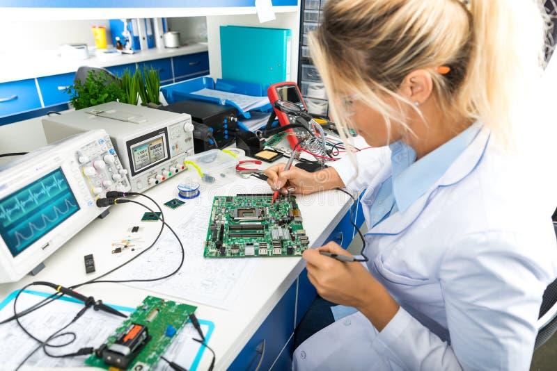 Женская материнская плата компьютера испытания электронного инженера в работе стоковые изображения