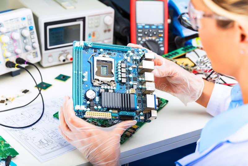 Женская материнская плата компьютера электронного инженера рассматривая в лаборатории стоковое изображение rf
