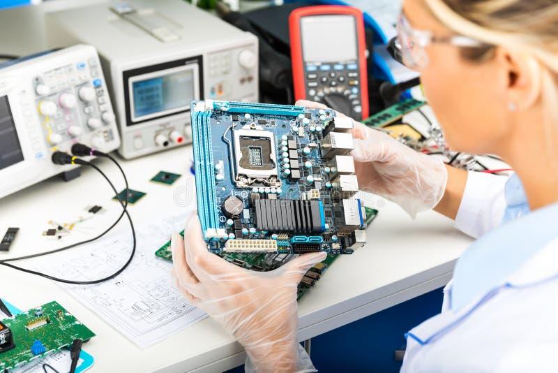 Женская материнская плата компьютера электронного инженера рассматривая в лаборатории стоковое изображение