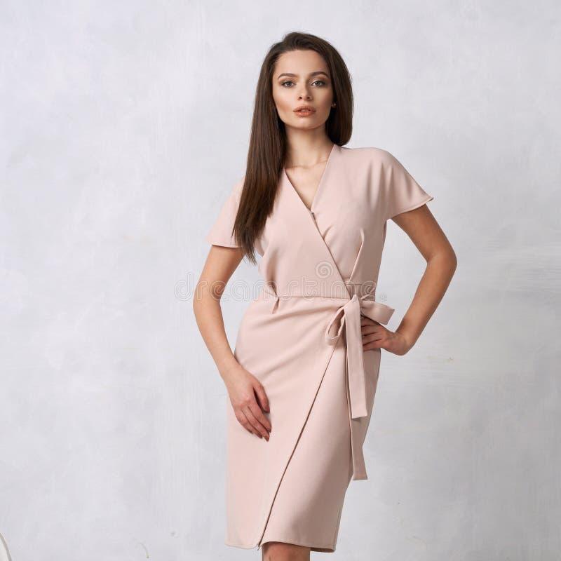 Женская модель в бежевом обруче вокруг платья midi стоковое фото