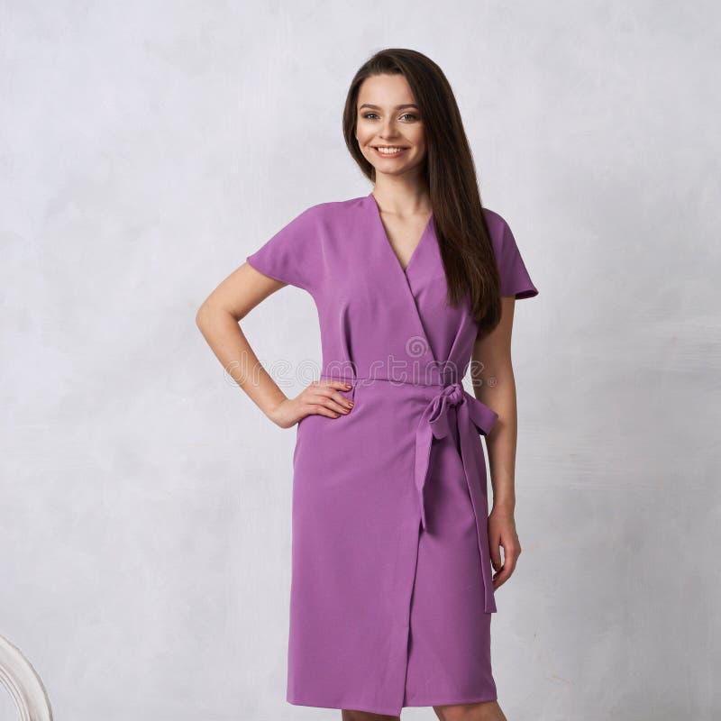 Женская модель в фиолетовом обруче вокруг платья midi стоковое изображение